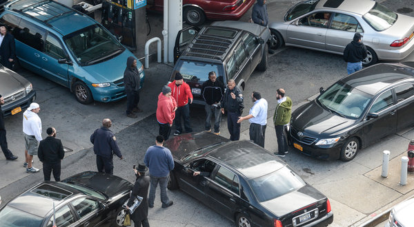 A gas station in Williamsburg, Brooklyn, had long lines on Thursday, and police officers to keep the peace. Officials said the fuel shortage would thin the taxi fleet. Credit: Robert Stolarik for The New York Times